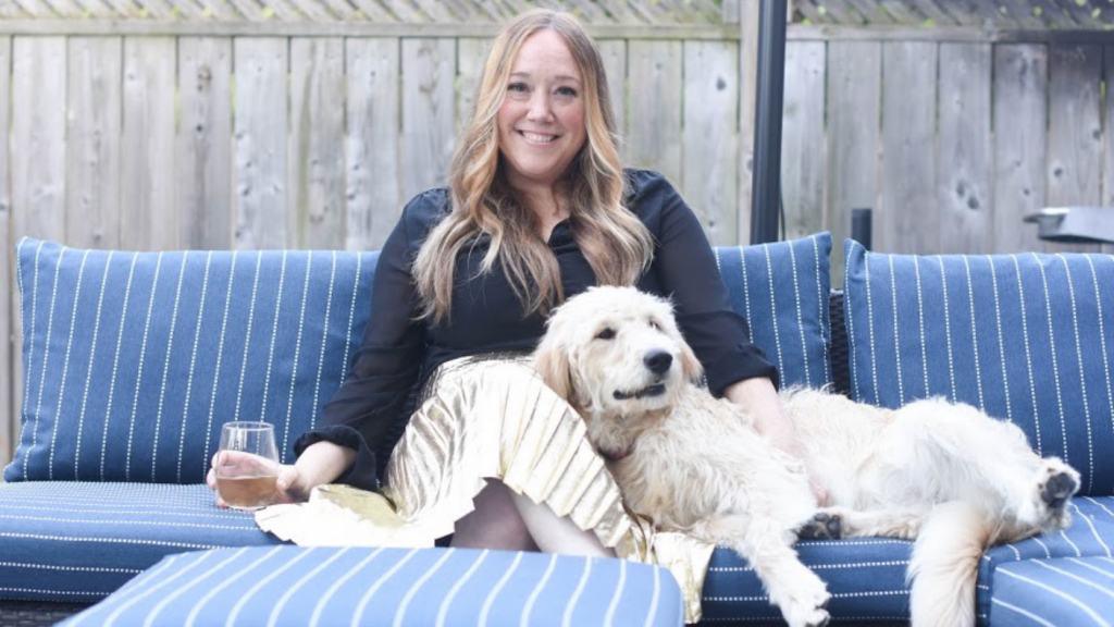 woman sitting with dog on patio cushions