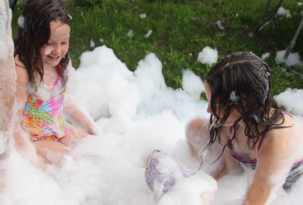 girls playing with diy foam machine