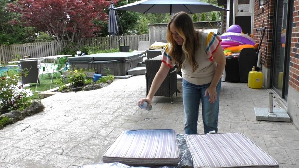woman spray painting patio cushion