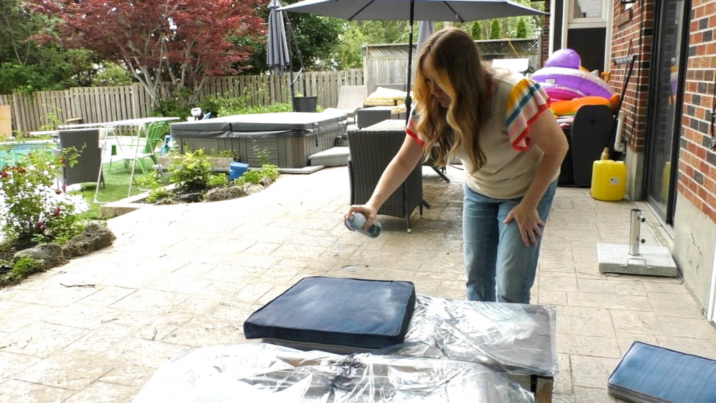 woman spray painting patio cushion outside
