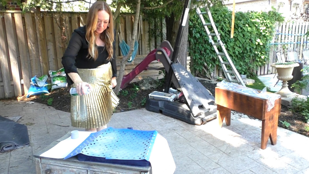 woman using stencil to update patio cushion